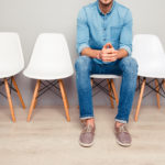 Man sitting on white chair surrounded by empty white chairs